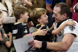 New Orleans Saints quarterback Drew Brees (9) greets his family after breaking the NFL all-time passing yards record in the first half of an NFL football game against the Washington Redskins in New Orleans, Monday, Oct. 8, 2018. (AP Photo/Bill Feig)