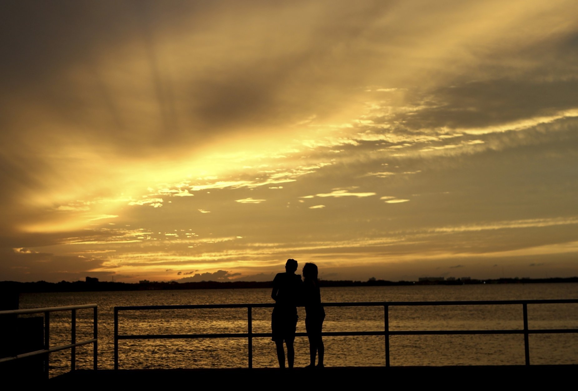 A couple is silhouetted against the sunset at the St. Andrews Marina in Panama City, Fla., Tuesday, Oct. 9, 2018, ahead of Hurricane Michael. (Patti Blake/News Herald via AP)