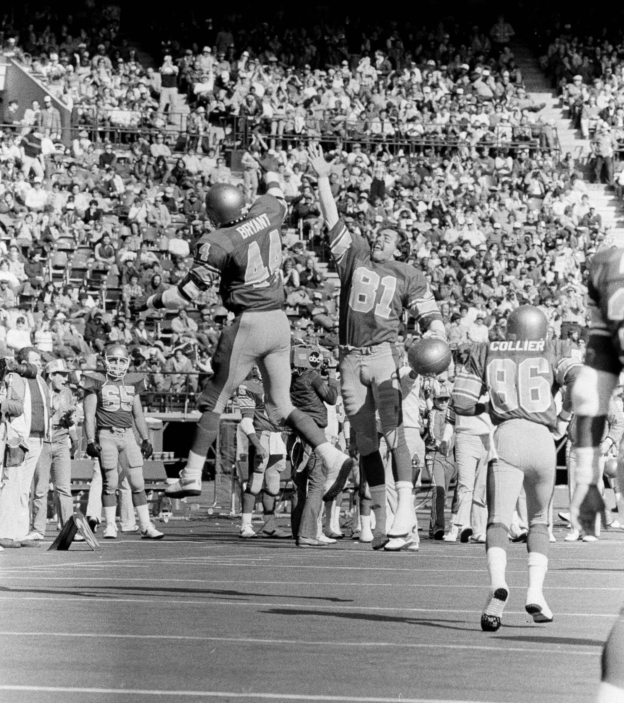Philadelphia Stars Kelvin Bryant, left, leaps in the air with teammate Scott Fitzkee for a high five in celebration of Bryant's second quarter touchdown against the New Jersey Generals at Veterans Stadium in Philadelphia, March 13, 1983. The former North Carolina player led his team to a 25-0 victory with 114 yards rushing. (AP Photo/George Widman)