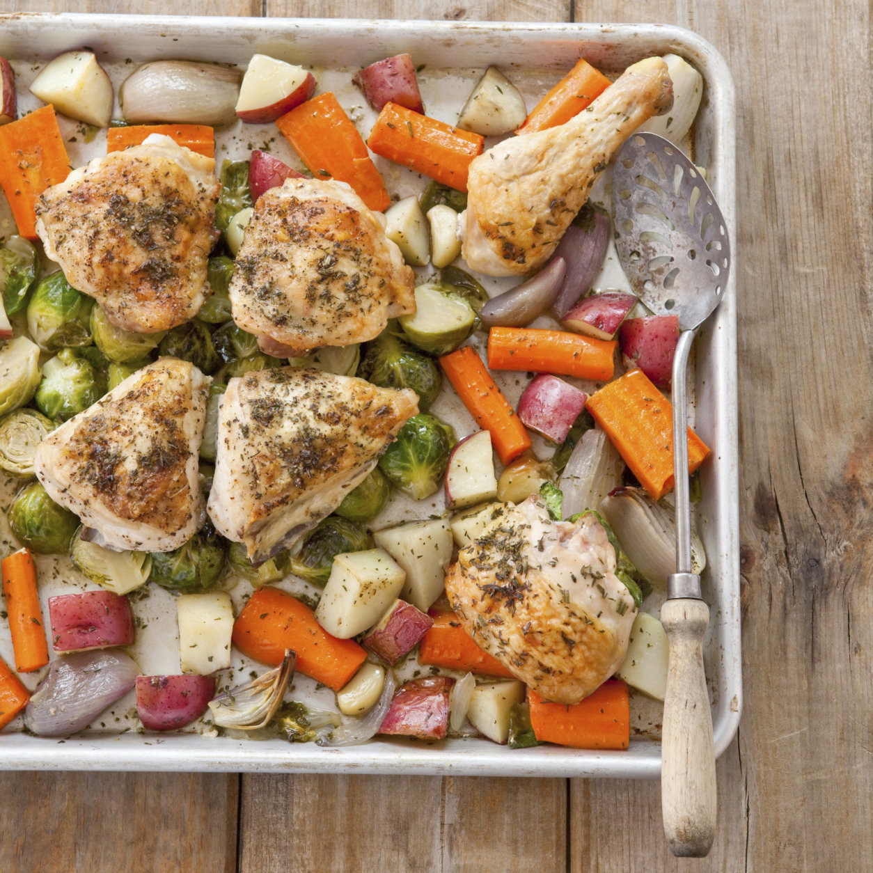 "This undated photo provided by America's Test Kitchen in May 2018 shows one-pan roasted chicken with root vegetables in Brookline, Mass. This recipe appears in the cookbook ""How to Roast Everything."" (Joe Keller/America's Test Kitchen via AP)"