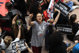 A demonstrator protests against Supreme Court nominee Brett Kavanaugh and chant slogans during a rally in the atrium of the Hart Senate Office Building on Capitol Hill in Washington, Thursday, Oct. 4, 2018. (AP Photo/Manuel Balce Ceneta)