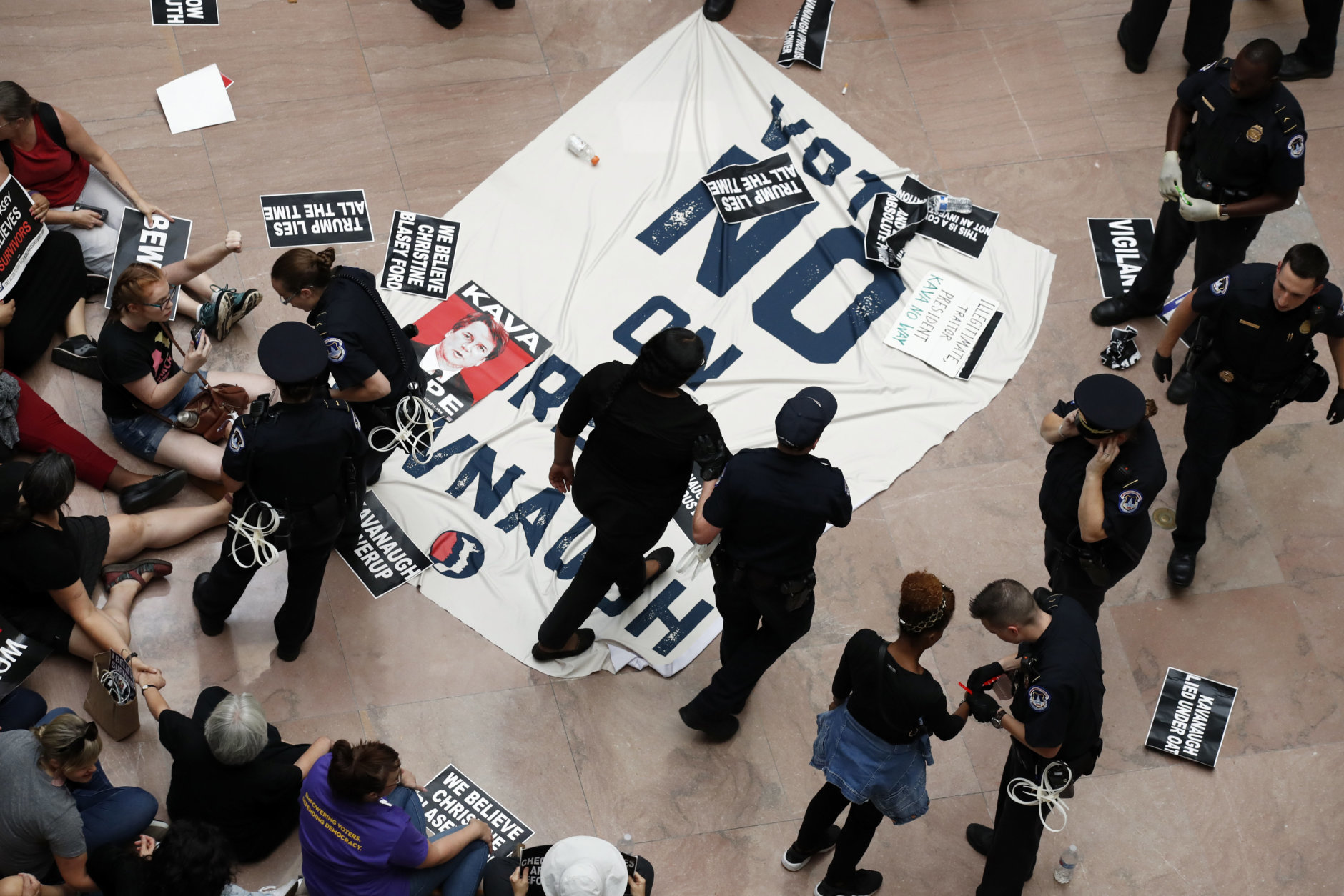 Protesters against Supreme court nominee Brett Kavanaugh are arrested by Capitol Hill Police in the atrium of the Hart Senate Office Building on Capitol Hill, Thursday, Oct. 4, 2018 in Washington. (AP Photo/Alex Brandon)