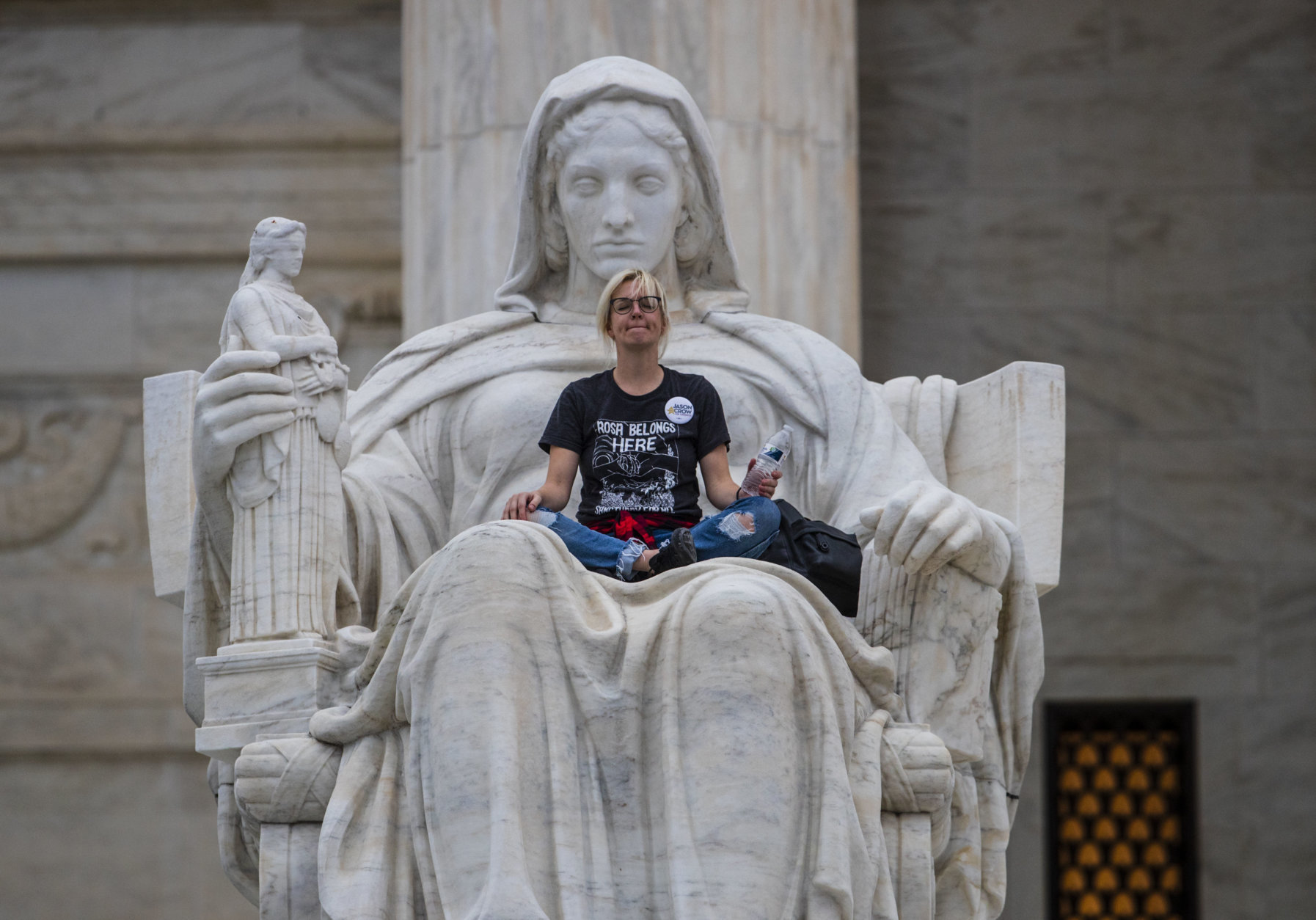 Jessica Campbell-Swanson, an activist from Denver, sits in the lap of a sculpture known as the Statue of Contemplation of Justice on the steps of the Supreme Court Building where she and others protested the confirmation of Brett Kavanaugh as the high court's newest justice, in Washington, Saturday, Oct. 6, 2018. Kavanaugh took the oath inside the building after the bitterly polarized U.S. Senate narrowly confirmed him, delivering an election-season triumph to President Donald Trump that could swing the court rightward for a generation. (AP Photo/J. Scott Applewhite)