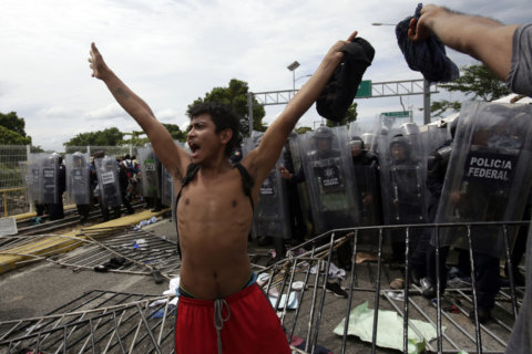 Migrant caravan clashes with Mexican police, waits on bridge at Guatemalan-Mexican border