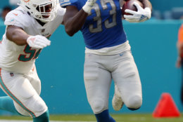 Detroit Lions running back Kerryon Johnson (33) carries the ball as Miami Dolphins linebacker Raekwon McMillan (52) attempts to tackle, during the first half of an NFL football game against the Miami Dolphins, Sunday, Oct. 21, 2018, in Miami Gardens, Fla. (AP Photo/Wilfredo Lee)