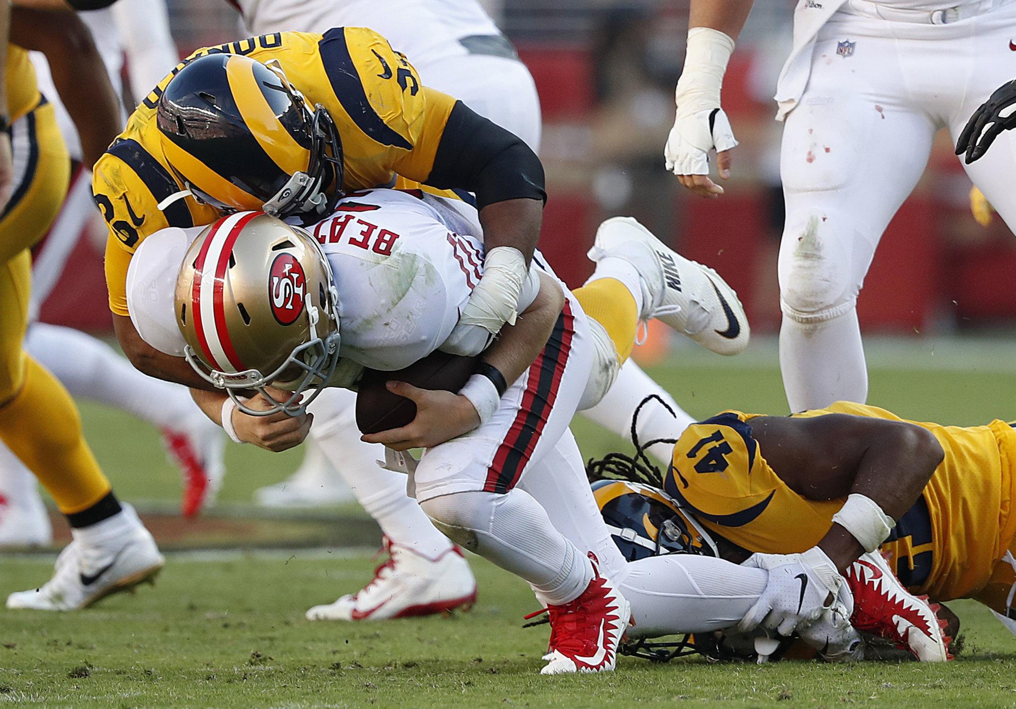 Los Angeles Rams defensive tackle Aaron Donald, top, sacks San Francisco 49ers quarterback C.J. Beathard during the second half of an NFL football game in Santa Clara, Calif., Sunday, Oct. 21, 2018. (AP Photo/Tony Avelar)