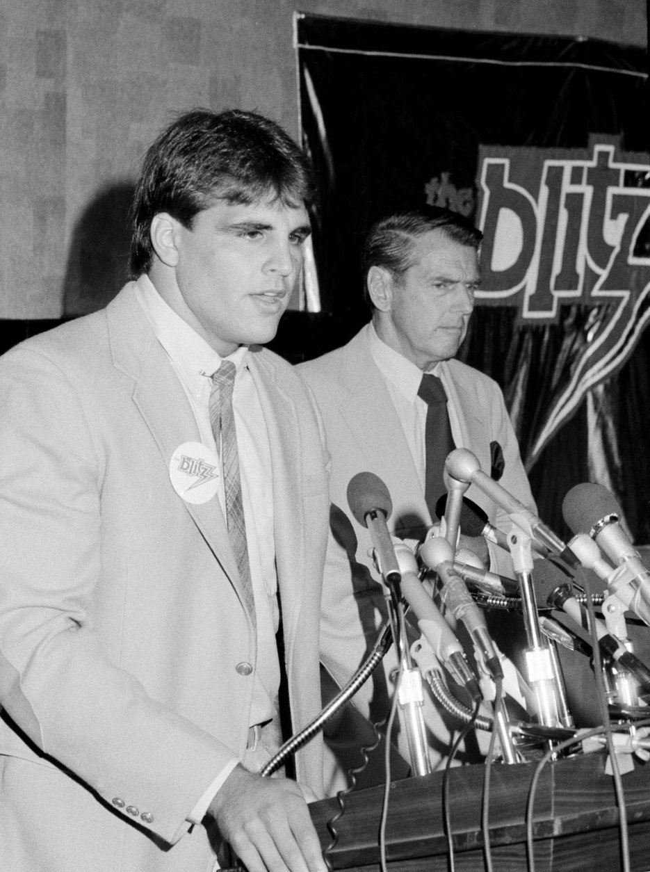 """Tim Wrightman, left, former UCLA tight end and a third round draft choice of the Chicago Bears, announces at a press conference in Chicago, Ill., that he has signed a two-year contract with the Chicago Blitz of the newly-formed USFL, Aug. 6, 1982. George Allen, right, said the signing was a """"historic day, he's the first major player signed by the league, the first with total credibility."""" Allen will be the coach of the Blitz. (AP Photo/Charles Knoblock)"""
