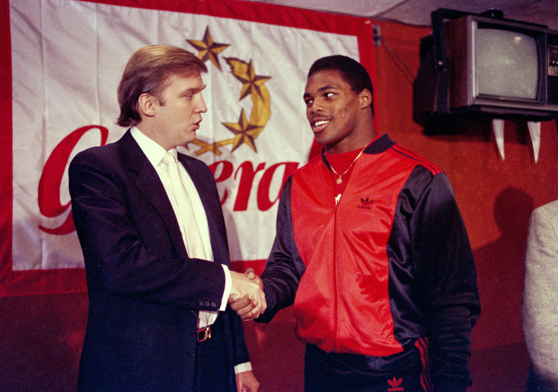 FILE - In this March 8, 1984, file photo, Donald Trump shakes hands with Herschel Walker in New York after agreement on a 4-year contract with the New Jersey Generals USFL football team. The New Jersey Generals have been largely forgotten, but Trump's ownership of the team was formative in his evolution as a public figure and peerless self-publicist. With money and swagger, he led a shaky and relatively low-budget spring football league, the USFL, into a showdown with the NFL. (AP Photo/Dave Pickoff, File)