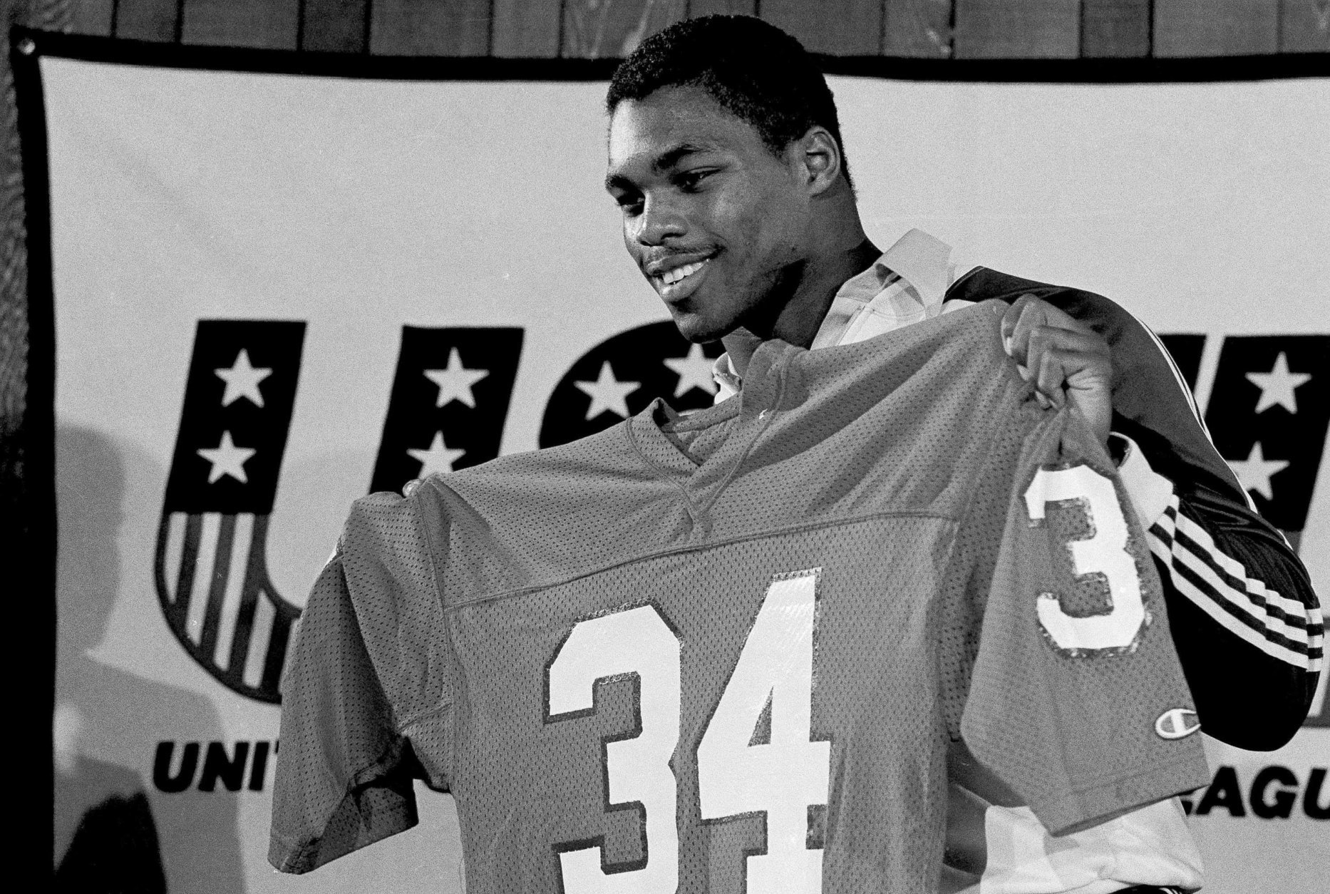 Former Georgia football player Herschel Walker holds up his new jersey at a press conference in Orlando, Fla., Feb. 26, 1983. Walker joined the New Jersey Generals of the USFL and worked out for the first time at their spring camp at the University of Central Florida. (AP Photo/Ron Lindsey)