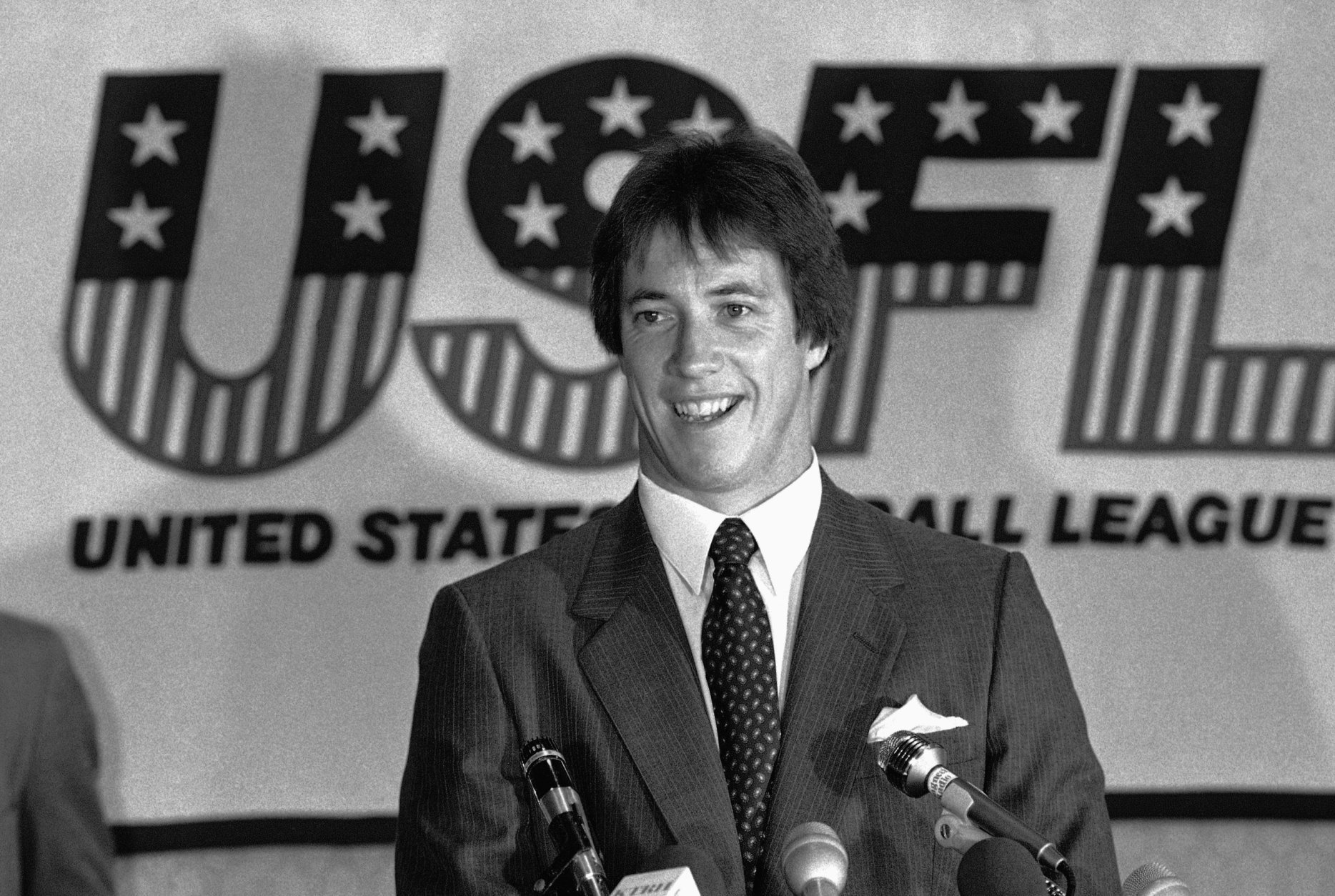 University of Miami quarterback Jim Kelly is all smiles at his press conference, Thursday, June 10, 1983 after signing a multi-year contract with the new USFL franchise, the Houston Gamblers. His college teammate running back Mark Rush also signed with the Gamblers. Both were drafted by NFL clubs. (AP Photo/F. Carter Smith)