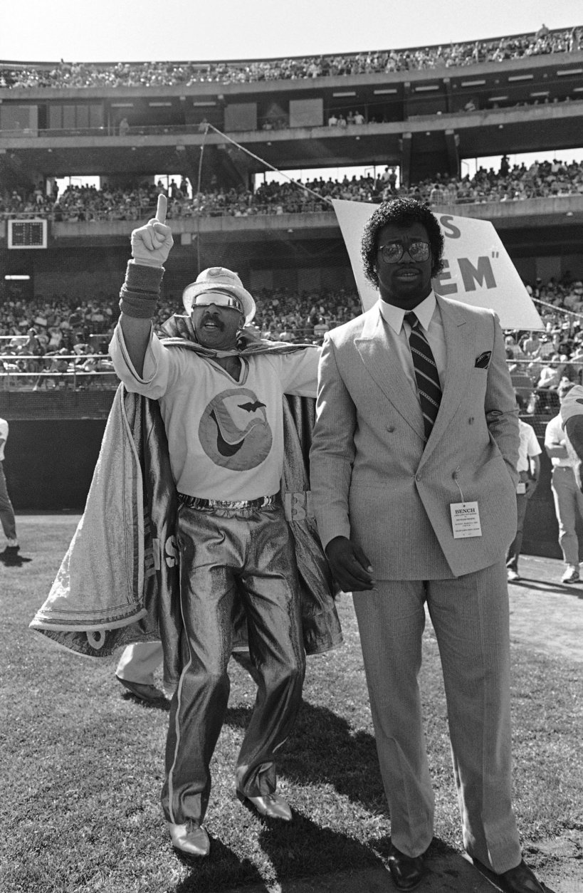 The New Orleans Breakers newly-acquired running back Marcus Dupree stands with the team mascot on the sidelines prior to the Breakers USFL game against the Invaders in Oakland on Sunday, March 5, 1984. Dupree just signed a $6 million dollar contract with the New Orleans club. Dupree last played football for Oklahoma before quitting the team. (AP Photo/Eric Risberg)