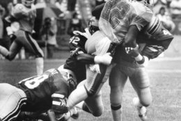 Running back Marcus Dupree (22) of the New Orleans Breakers, gets caught in a crowd of Washington Federals defenders during the first half of game on Sunday, June 24, 1984 at Robert F. Kennedy Stadium in Washington. The Federals topped the contest 20-17. (AP Photo/Richard Folkers)