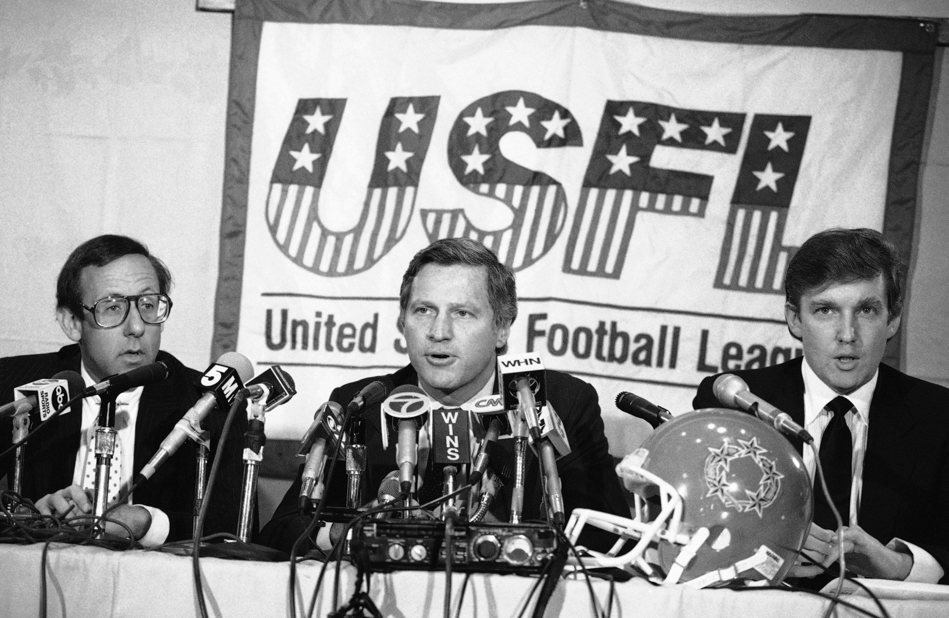 New York real estate magnates Stephen Ross, left, and Donald Trump, right, speak about the agreement they have reached in principle to merge the Houston Gamblers and New Jersey Generals football franchises, Thursday, August 2, 1985 in New York. USFL Commissioner Harry L. Usher, center announced the agreement. (AP Photo/Marty Lederhandler)