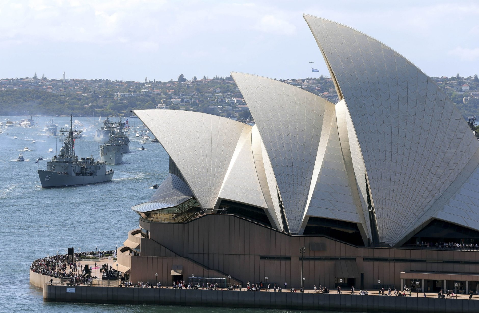 FILE - In this Oct. 4, 2013, file photo, the Opera House is seen as Australian warships from front, HMAS Sydney, Darwin and Perth enter the harbour in Sydney, Australia, during the International Fleet review.  Minister for Cities, Urban Infrastructure and Population Alan Tudge said Tuesday, Oct. 9, 2018, that his government wants to cut the number of immigrants moving to Sydney and Melbourne in a bid to reduce congestion in Australia's two biggest cities. (AP Photo/Rob Griffith, File)