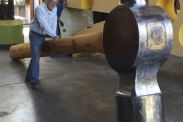In this April 2017 photo released by Doug Unkrey, artist Unkrey poses for a photo with a large hammer he created at his studio in Geyserville, Calif. The Santa Rosa Press-Democrat says police in Healdsburg in California's wine country are looking for the enormous artwork that vanished in the first weekend of October 2018. (Erika Linn via AP)