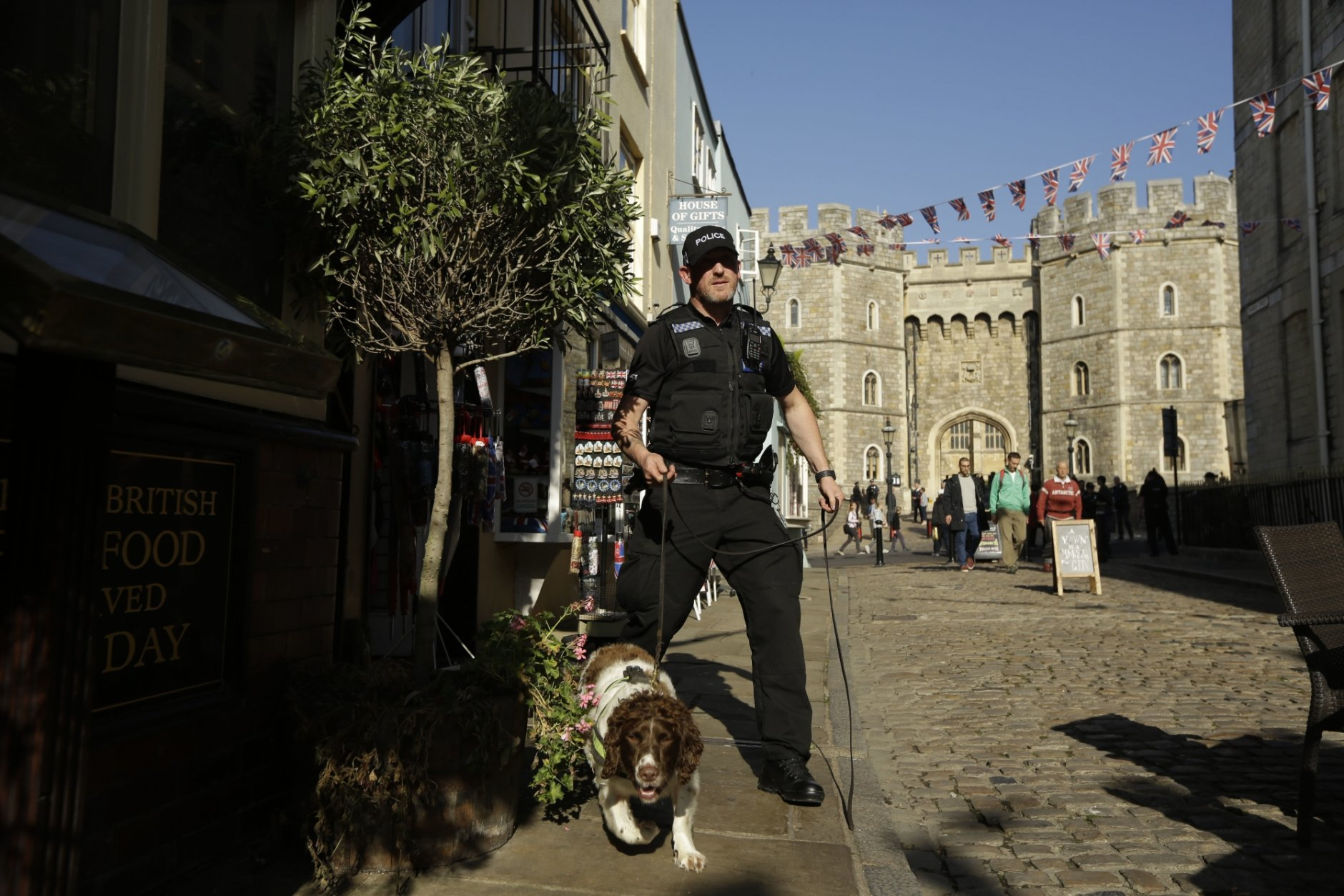 A police search dog and handler patrol outside Windsor Castle ahead of the wedding of Britain's Princess Eugenie in Windsor, England, Wednesday, Oct. 10, 2018. The 28-year-old granddaughter of Queen Elizabeth II is due to marry liquor company executive Jack Brooksbank on Friday in St. George's Chapel at Windsor Castle. (AP Photo/Matt Dunham)