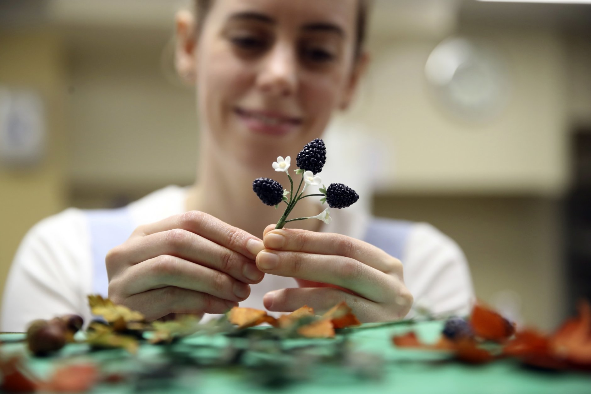 Baker Sophie Cabot puts the finishing touches to cake decorations for the red velvet and chocolate wedding cake for Britian's Princess Eugenie and Mr Brooksbank, in the kitchens at Buckingham Palace, London, Wednesday Oct. 10, 2018. The granddaughter of Queen Elizabeth II is due to marry liquor company executive Jack Brooksbank on Friday in St. George's Chapel at Windsor Castle. (Chris Jackson/Pool via AP)