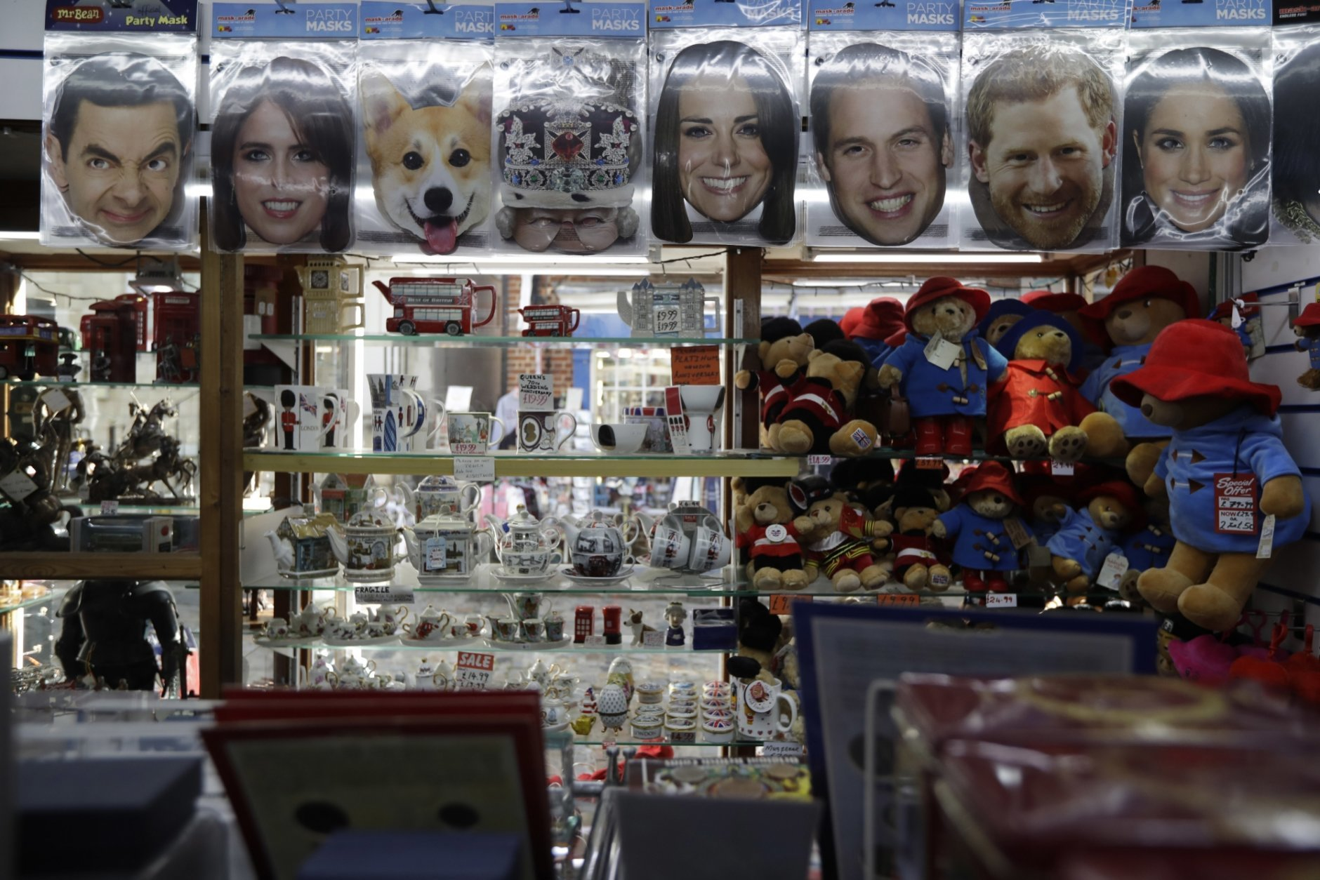 A Princess Eugenie mask, second left, is displayed for sale with other masks in a souvenir shop ahead of the wedding of Britain's Princess Eugenie in Windsor, England, Wednesday, Oct. 10, 2018. The 28-year-old granddaughter of Queen Elizabeth II is due to marry liquor company executive Jack Brooksbank on Friday in St. George's Chapel at Windsor Castle. (AP Photo/Matt Dunham)