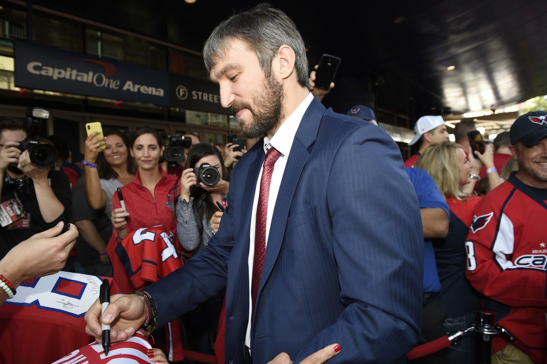 c76cad10 Washington Capitals' Alex Ovechkin, center, of Russia, signs for fans as he