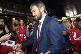 Washington Capitals' Alex Ovechkin, center, of Russia, signs for fans as he walks the red carpet before their opening season NHL hockey game against the Boston Bruins, Wednesday, Oct. 3, 2018, in Washington. (AP Photo/Nick Wass)