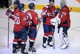 Washington Capitals goaltender Braden Holtby (70) celebrates with Evgeny Kuznetsov (92), of Russia; Dmitry Orlov (9), of Russia; Lars Eller (20), of Denmark; and Nic Dowd (26) after an NHL hockey game against the Boston Bruins, Wednesday, Oct. 3, 2018, in Washington. The Capitals won 7-0. (AP Photo/Nick Wass)