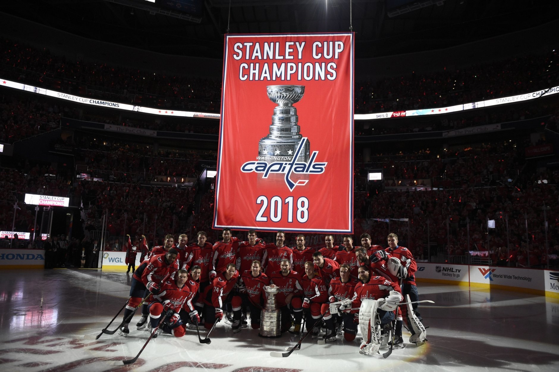 4a9cf78f The Washington Capitals pose under the Stanley Cup champions banner before  the team's NHL hockey game