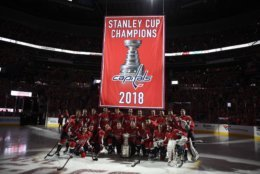 The Washington Capitals pose under the Stanley Cup champions banner before the team's NHL hockey game against the Boston Bruins, Wednesday, Oct. 3, 2018, in Washington. (AP Photo/Nick Wass)