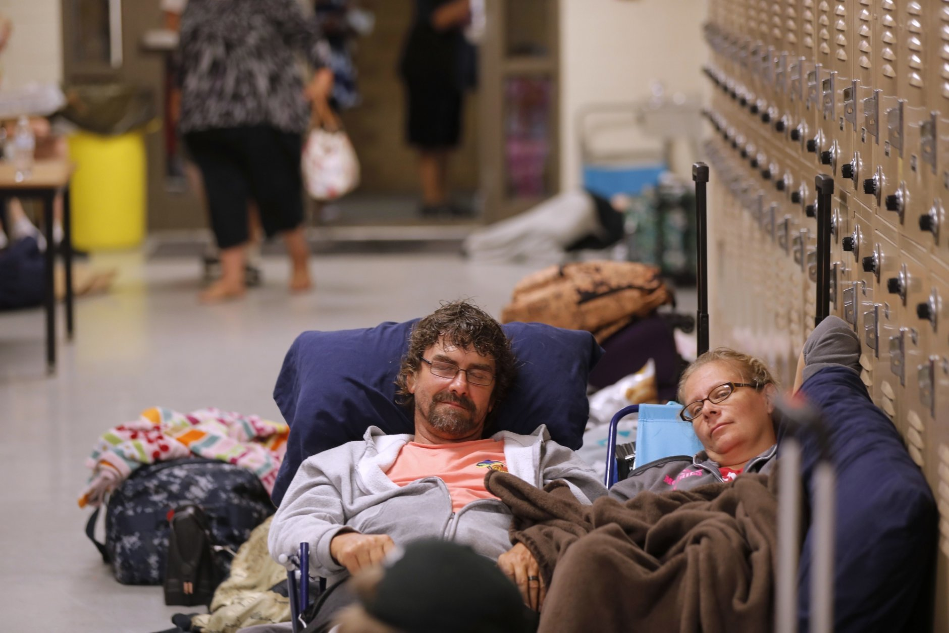 CORRECTS NAME OF HURRICANE TO MICHAEL FROM MATTHEW - Jeff Ready and his wife Julie Ready rest in a a hallway at an evacuation shelter set up at Rutherford High School, in advance of Hurricane Michael, which is expected to make landfall today, in Panama City Beach, Fla., Wednesday, Oct. 10, 2018. (AP Photo/Gerald Herbert)