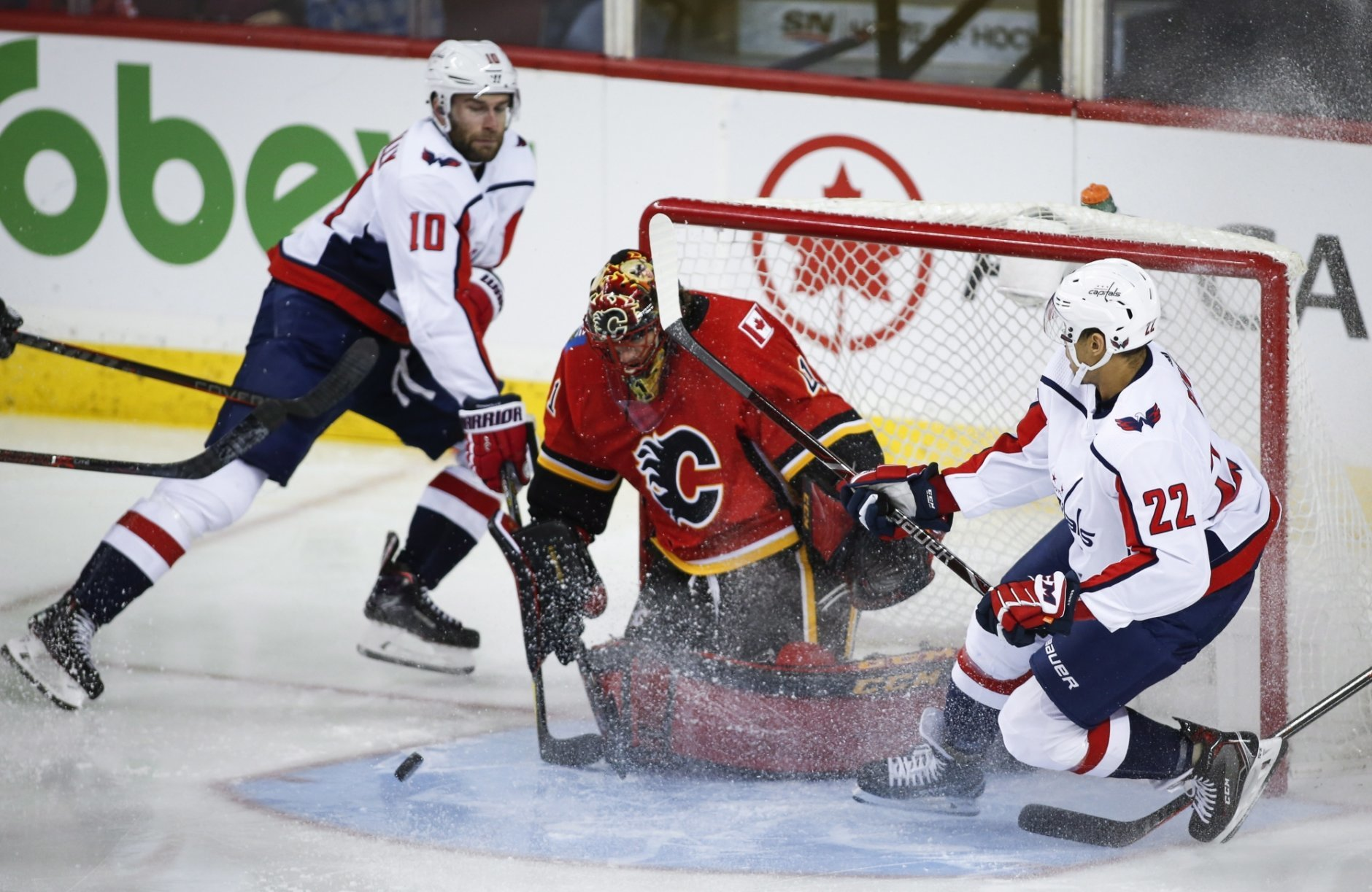 Washington Capitals' Brett Connolly, left, and teammate Madison Bowey, right, pressure Calgary Flames goalie Mike Smith during third-period NHL hockey game action in Calgary, Alberta, Saturday, Oct. 27, 2018. (Jeff McIntosh/The Canadian Press via AP)