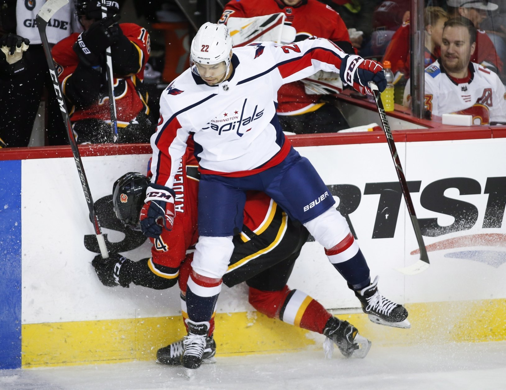 Washington Capitals' Madison Bowey, right, checks Calgary Flames' Rasmus Andersson, of Sweden, during second period NHL hockey action in Calgary, Alberta, Saturday, Oct. 27, 2018. (Jeff McIntosh/The Canadian Press via AP)