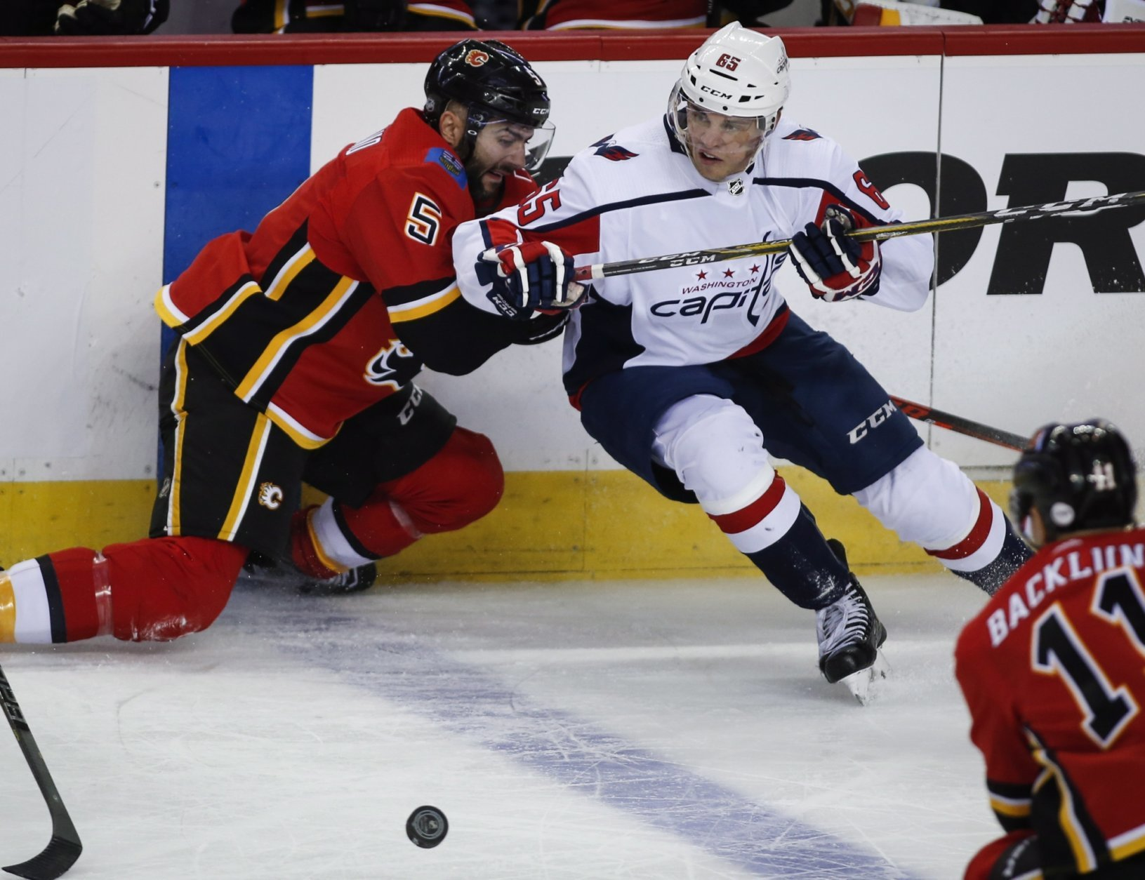 Washington Capitals' Andre Burakovsky, right, of Austria, gets past Calgary Flames' Mark Giordano during the first period of an NHL hockey game in Calgary, Alberta Saturday, Oct. 27, 2018. (Jeff McIntosh/The Canadian Press via AP)