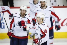 Washington Capitals' Nicklas Backstrom, center, of Sweden, celebrates his winning goal with teammates during shootout NHL hockey action against the Calgary Flames in Calgary, Alberta, Saturday, Oct. 27, 2018. (Jeff McIntosh/The Canadian Press via AP)