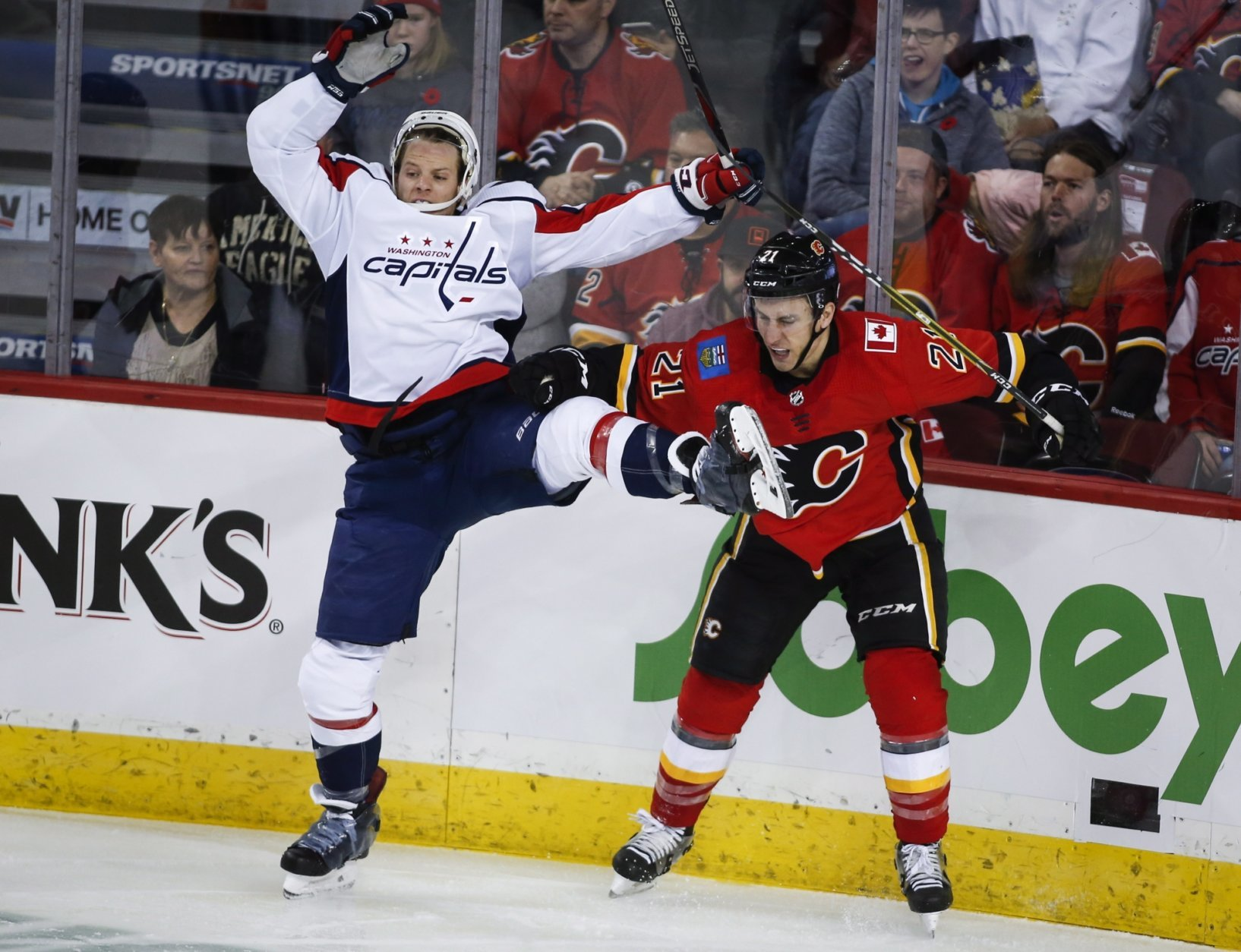 Washington Capitals' Nic Dowd, left, is checked Calgary Flames' Garnet Hathaway during second period NHL hockey action in Calgary, Alberta, Saturday, Oct. 27, 2018. (Jeff McIntosh/The Canadian Press via AP)