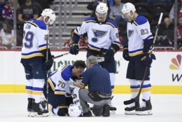 FILE - In this Sept. 30, 2018, file photo, St. Louis Blues center Oskar Sundqvist (70), of Sweden, is tended to by a trainer after he was checked by Washington Capitals right wing Tom Wilson, not seen, during the second period of an NHL preseason hockey game,in Washington. Also seen are Blues defenseman Vince Dunn (29), St. Louis Blues left wing Mackenzie MacEachern (62) and St. Louis Blues right wing Dmitrij Jaskin (23), of Russia. Wilson has been suspended 20 games by the NHL for a blindside hit to the head of an opponent during a preseason game. Wilson's punishment was announced Wednesday, Oct. 3, 2018, just hours before the reigning Stanley Cup champion Capitals were to raise their banner and open their title defense by hosting the Boston Bruins to begin the regular season. (AP Photo/Nick Wass, File)