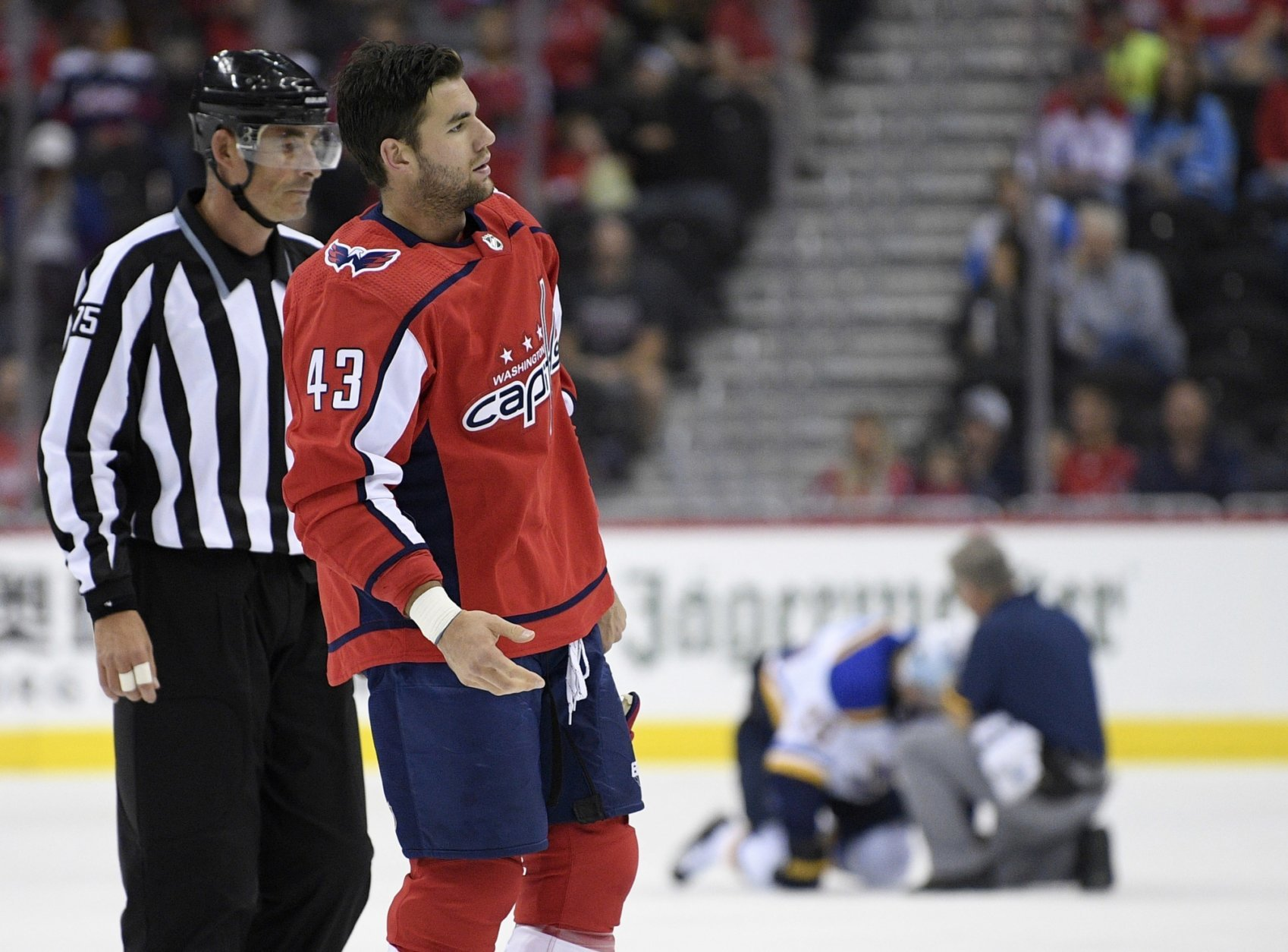 FILE - In this Sept. 30, 2018, file photo, Washington Capitals right wing Tom Wilson (43) is escorted by an official off the ice after he checked St. Louis Blues center Oskar Sundqvist, on ice at back center, during the second period of an NHL preseason hockey game, in Washington. Wilson has been suspended 20 games by the NHL for a blindside hit to the head of an opponent during a preseason game. Wilson's punishment was announced Wednesday, Oct. 3, 2018, just hours before the reigning Stanley Cup champion Capitals were to raise their banner and open their title defense by hosting the Boston Bruins to begin the regular season. (AP Photo/Nick Wass, File)