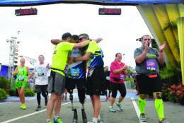 Cedric King is congratulated at the finish line at the Walt Disney World Marathon. (Phelan M. Ebenhack)