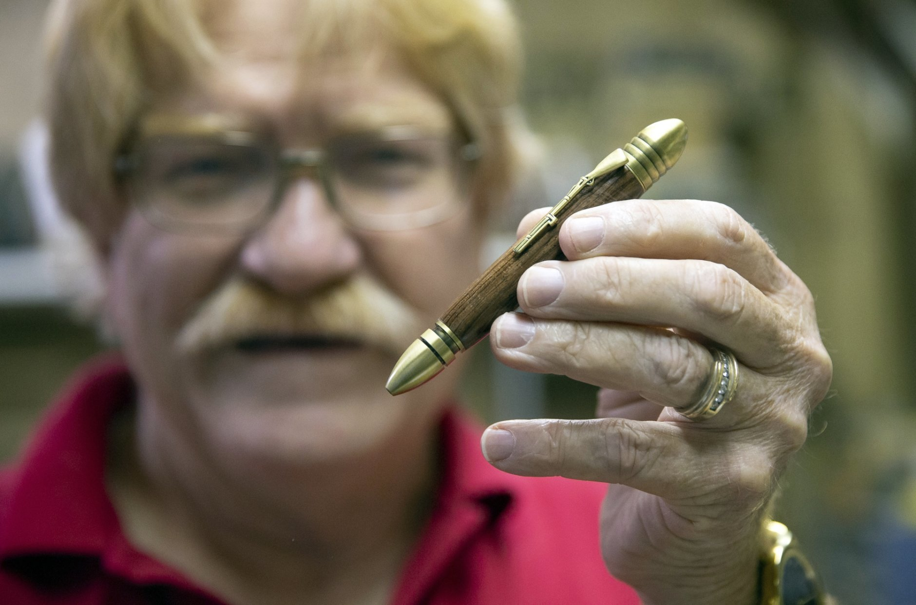 Ed Seyfried, owner of Ed's Pens, holds a Civil War pen he made at his home in King George, Va. on Sept. 20, 2018. Seyfried uses materials including wood, acrylic, metal, horn and bone to make the pens. (Mike Morones/The Free Lance-Star via AP)