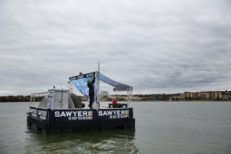Todd Phillips, founder and director of The Last Well, makes a repair on day eight on his wooden barge on Lake Ray Hubbard in Rockwall, Texas on Wednesday, Oct. 17, 2018. Phillips is planning to stay on the barge until he is able to raise $2 million for Liberians to have clean water. (Rose Baca/The Dallas Morning News via AP)