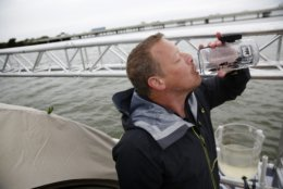 Todd Phillips, founder and director of The Last Well, drinks filtered water for the lake on day eight on his wooden barge on Lake Ray Hubbard in Rockwall, Texas on Wednesday, Oct. 17, 2018. Phillips is planning to stay on the barge until he is able to raise $2 million for Liberians to have clean water.  (Rose Baca/The Dallas Morning News via AP)