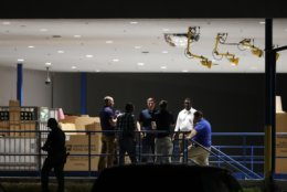 People gather on a loading dock at a postal facility, Thursday, Oct. 25, 2018, in Opa-Locka, Fla. Investigators searched coast-to-coast Thursday for the culprit and motives behind the bizarre mail-bomb plot aimed at critics of the president. (AP Photo/Wilfredo Lee)