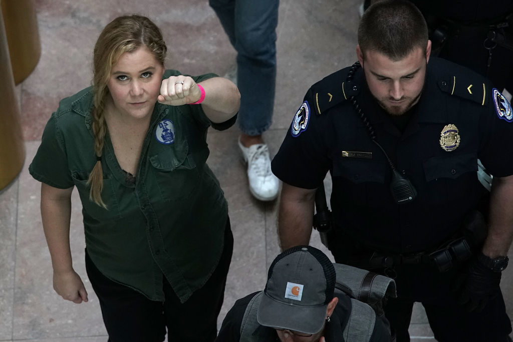 WASHINGTON, DC - OCTOBER 04:  Comedian Amy Schumer (L) is led away after she was arrested during a protest against the confirmation of Supreme Court nominee Judge Brett Kavanaugh October 4, 2018 at the Hart Senate Office Building on Capitol Hill in Washington, DC. Senators had an opportunity to review a new FBI background investigation into accusations of sexual assault against Kavanaugh and Republican leaders are moving to have a vote on his confirmation this weekend. (Photo by Alex Wong/Getty Images)