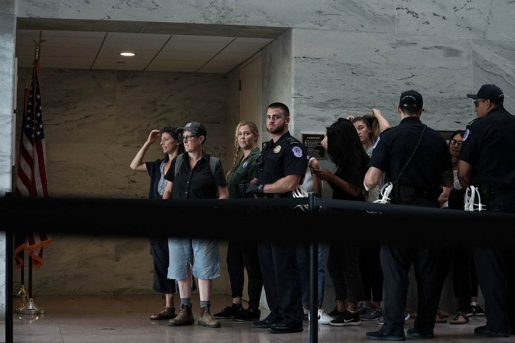 WASHINGTON, DC - OCTOBER 04:  Comedian Amy Schumer (C) waits to be led away after being arrested during a protest against the confirmation of Supreme Court nominee Judge Brett Kavanaugh October 4, 2018 at the Hart Senate Office Building on Capitol Hill in Washington, DC. Senators had an opportunity to review a new FBI background investigation into accusations of sexual assault against Kavanaugh and Republican leaders are moving to have a vote on his confirmation this weekend. (Photo by Alex Wong/Getty Images)