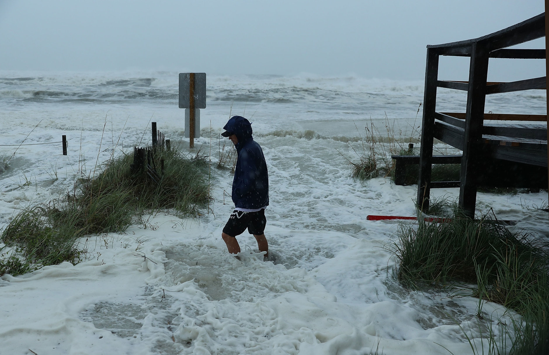 PANAMA CITY BEACH, FL - OCTOBER 10:  Cameron Sadowski walks along where waves are crashing onto the beach as the outer bands of  hurricane Michael arrive on October 10, 2018 in Panama City Beach, Florida. The hurricane is forecast to hit the Florida Panhandle at a possible category 4 storm.  (Photo by Joe Raedle/Getty Images)