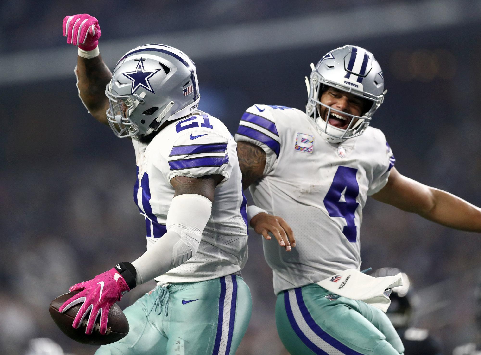 ARLINGTON, TX - OCTOBER 14:  Ezekiel Elliott #21 and Dak Prescott #4 of the Dallas Cowboys celebrate the fourth quarter touchdown against the Jacksonville Jaguars at AT&T Stadium on October 14, 2018 in Arlington, Texas.  (Photo by Ronald Martinez/Getty Images)