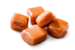 slightly melted toffee caramel candy close-up isolated (with clipping path) on white background