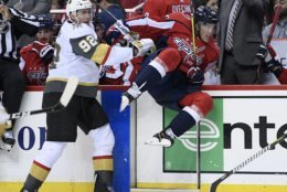 Vegas Golden Knights left wing Tomas Nosek (92) checks Washington Capitals right wing T.J. Oshie (77) during the second period of an NHL hockey game Wednesday, Oct. 10, 2018, in Washington. (AP Photo/Nick Wass)