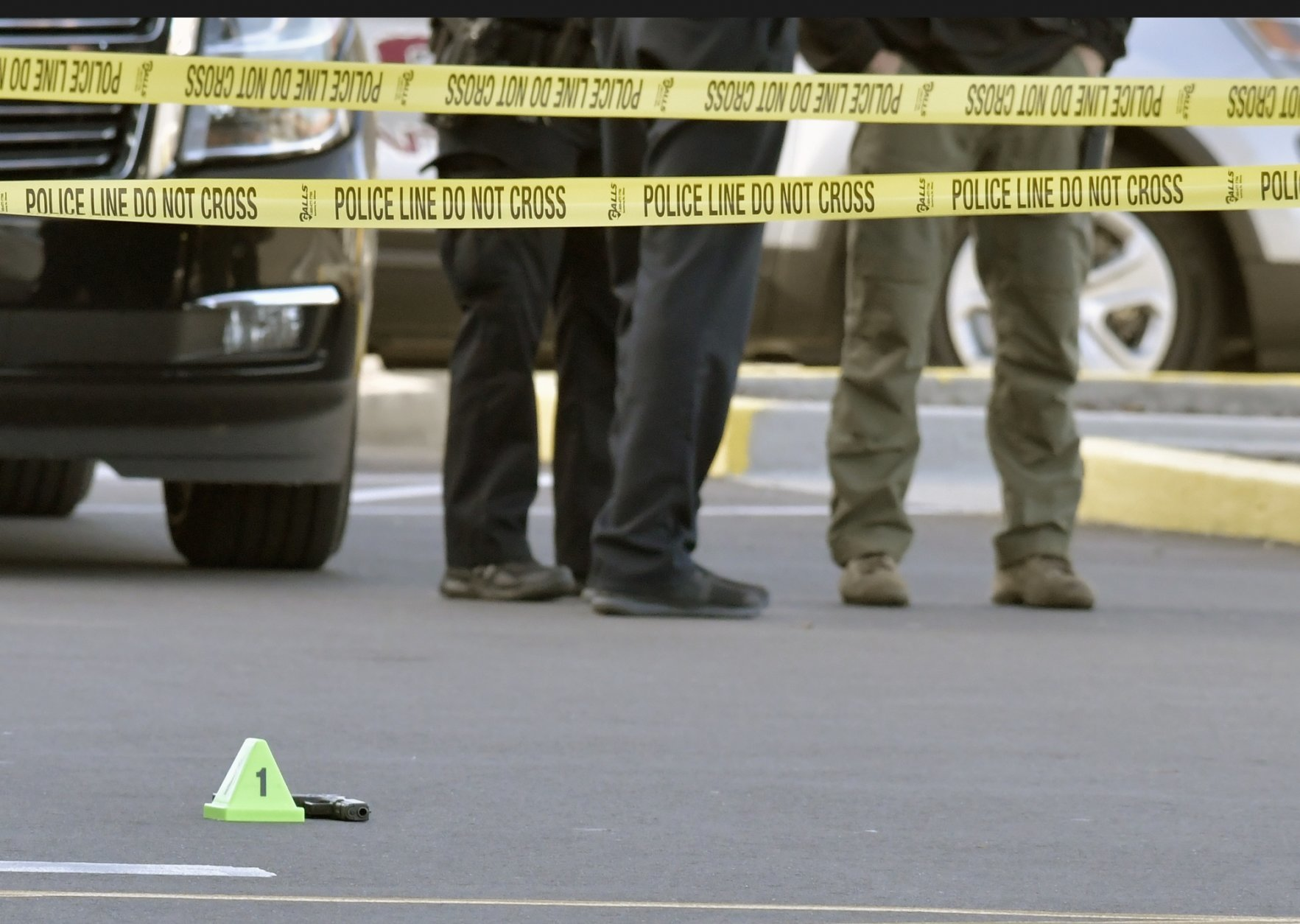 A gun lies on the ground inside a police barricade following a shooting at a Kroger grocery that left two people dead and a suspect in custody, Wednesday, Oct. 24, 2018, in Jeffersontown, Ky.  A male suspect fatally shot a man and a woman at a Kroger grocery store on the outskirts of Louisville, Kentucky, and then exchanged fire with an armed bystander before fleeing the scene, police said. He was captured shortly afterward. (AP Photo/Timothy D. Easley)