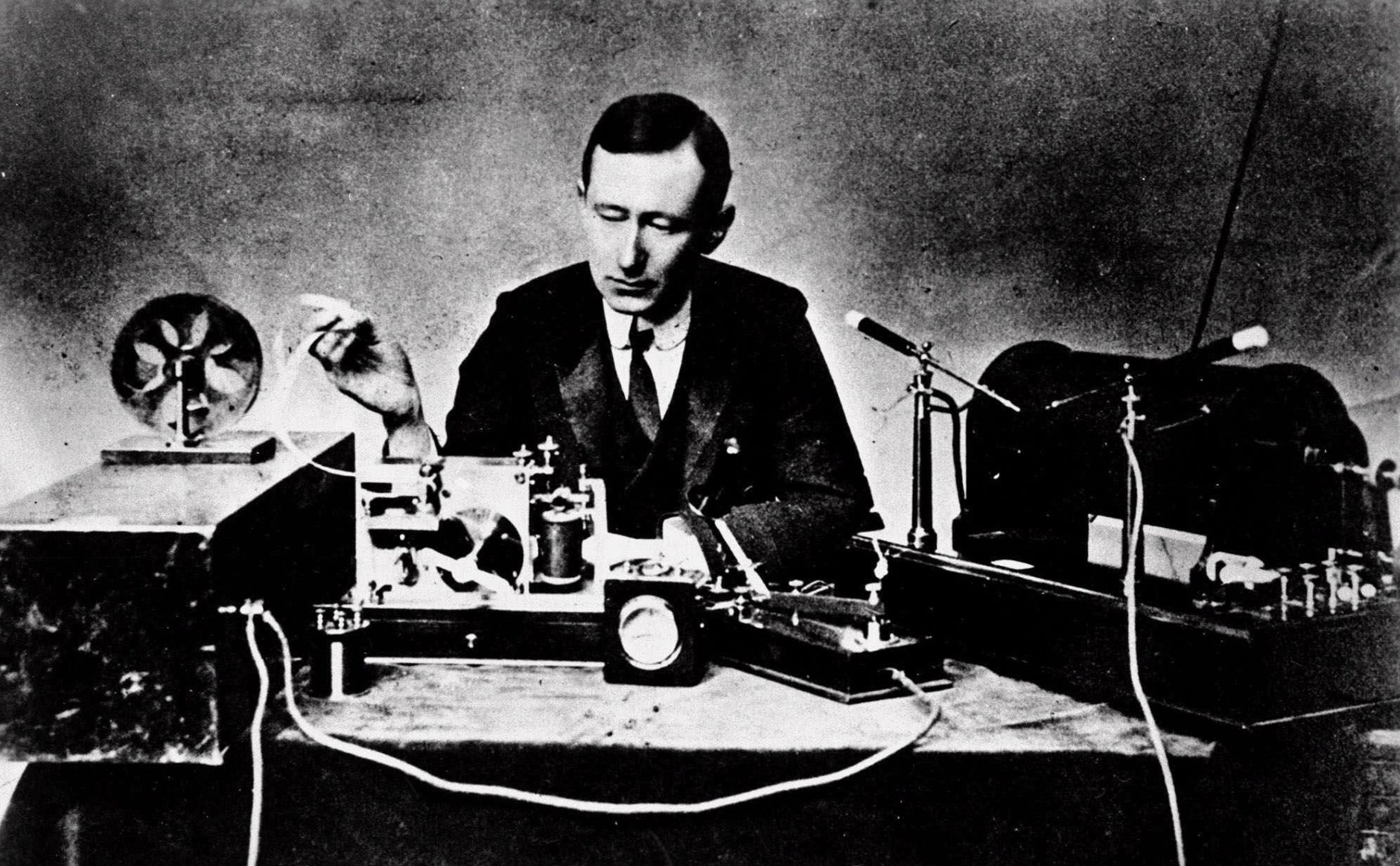 Italian physicist Guglielmo Marconi, who claimed he invented radio, reads signals on a tape recorder, left, with a 10-inch spark coil used for ship-to-shore radio tests in this 1901 photo.  (AP Photo)