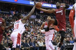 Miami Heat guard Dwyane Wade (3) is blocked by Washington Wizards center Ian Mahinmi (28) during the first half of an NBA basketball game, Thursday, Oct. 18, 2018, in Washington. Also seen is Wizards forward Otto Porter Jr. at back center. (AP Photo/Nick Wass)