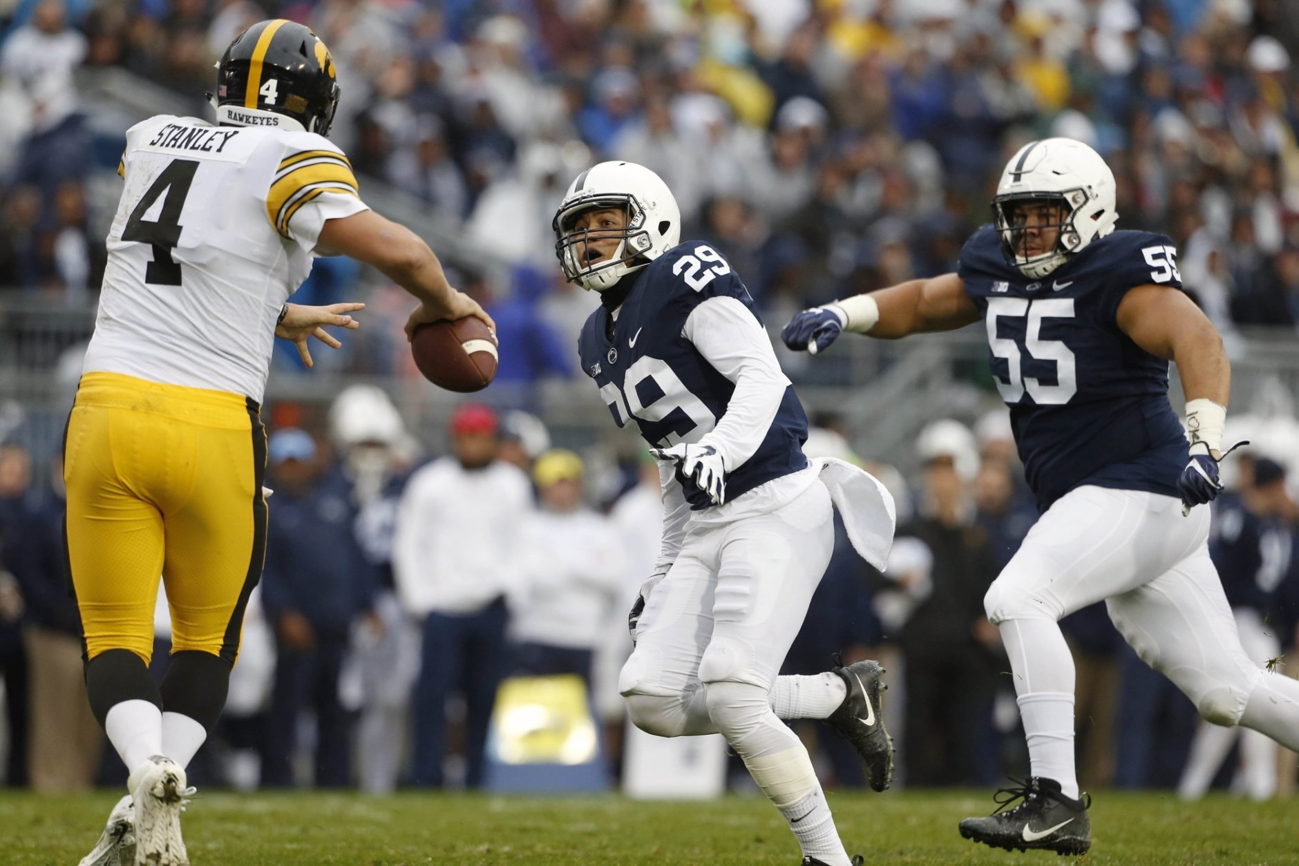 Penn State's John Reid (29) and Antonio Shelton (55) chase down Iowa quarterback Nate Stanley (4) during the first half of an NCAA college football game in State College, Pa., Saturday, Oct. 27, 2018. (AP Photo/Chris Knight)